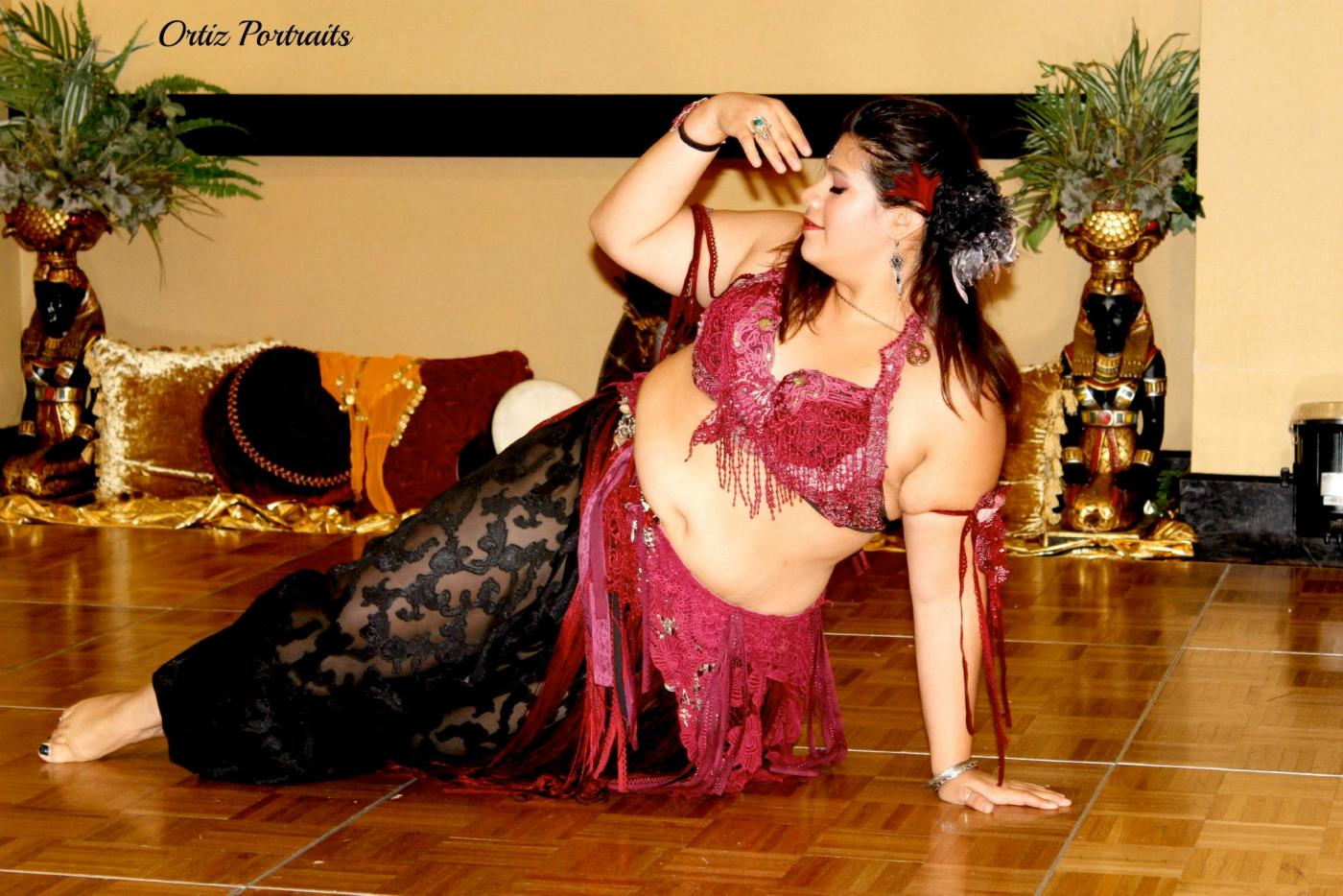 A woman in belly dancer attire strikes a dance pose