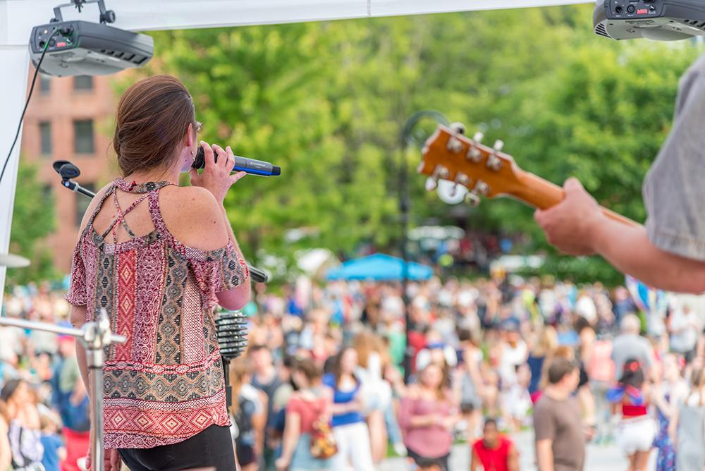 The back of a guitarist and a woman singing into a microphone on an outdoor stage in front of a crowd and summer trees.