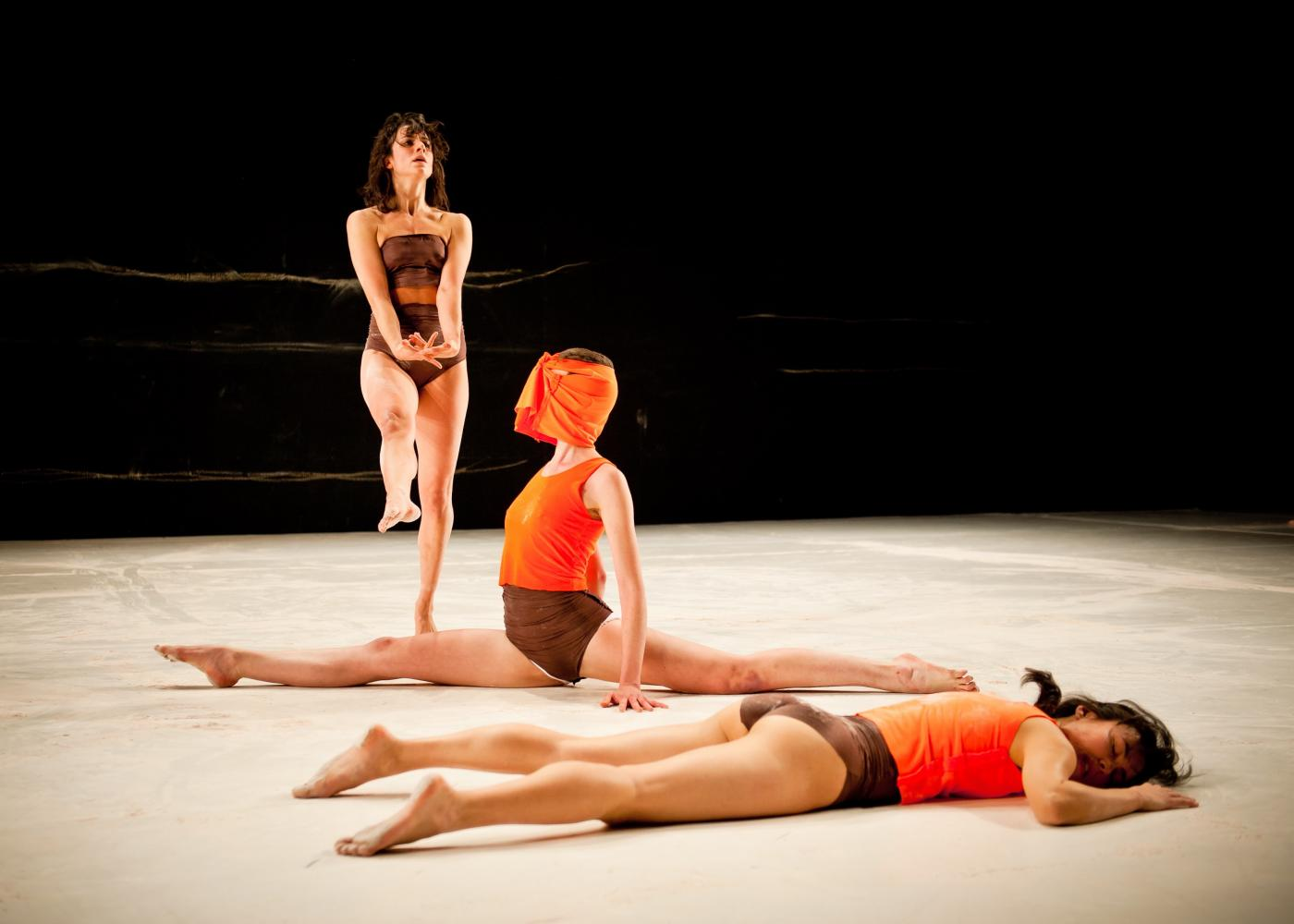 On a stage, three performers dance. Two of the performers wear bright orange costumes and do floor work. One hops in a red leotard.