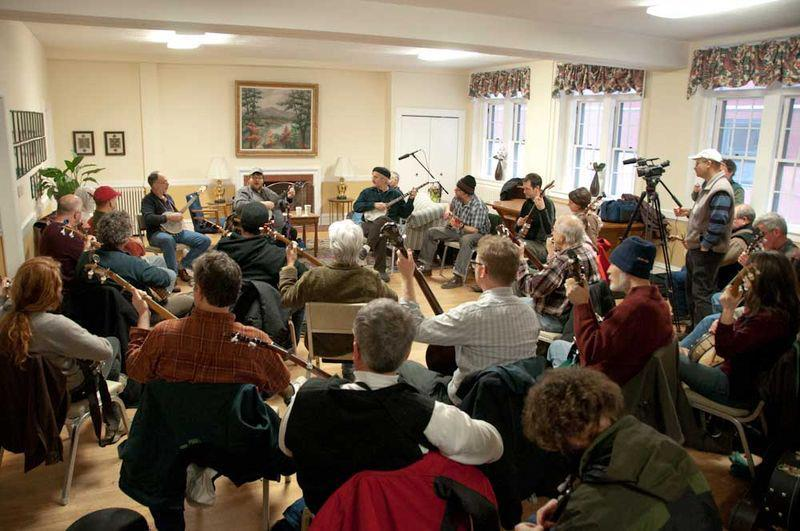 Inside a bright room, a group of thirty adults sit in a circle playing banjos.