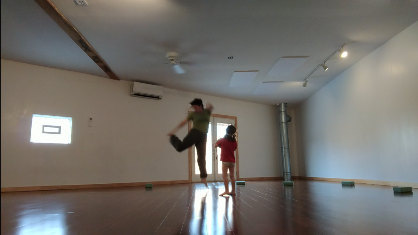 In a dance studio, a dancer leaps next to a child.