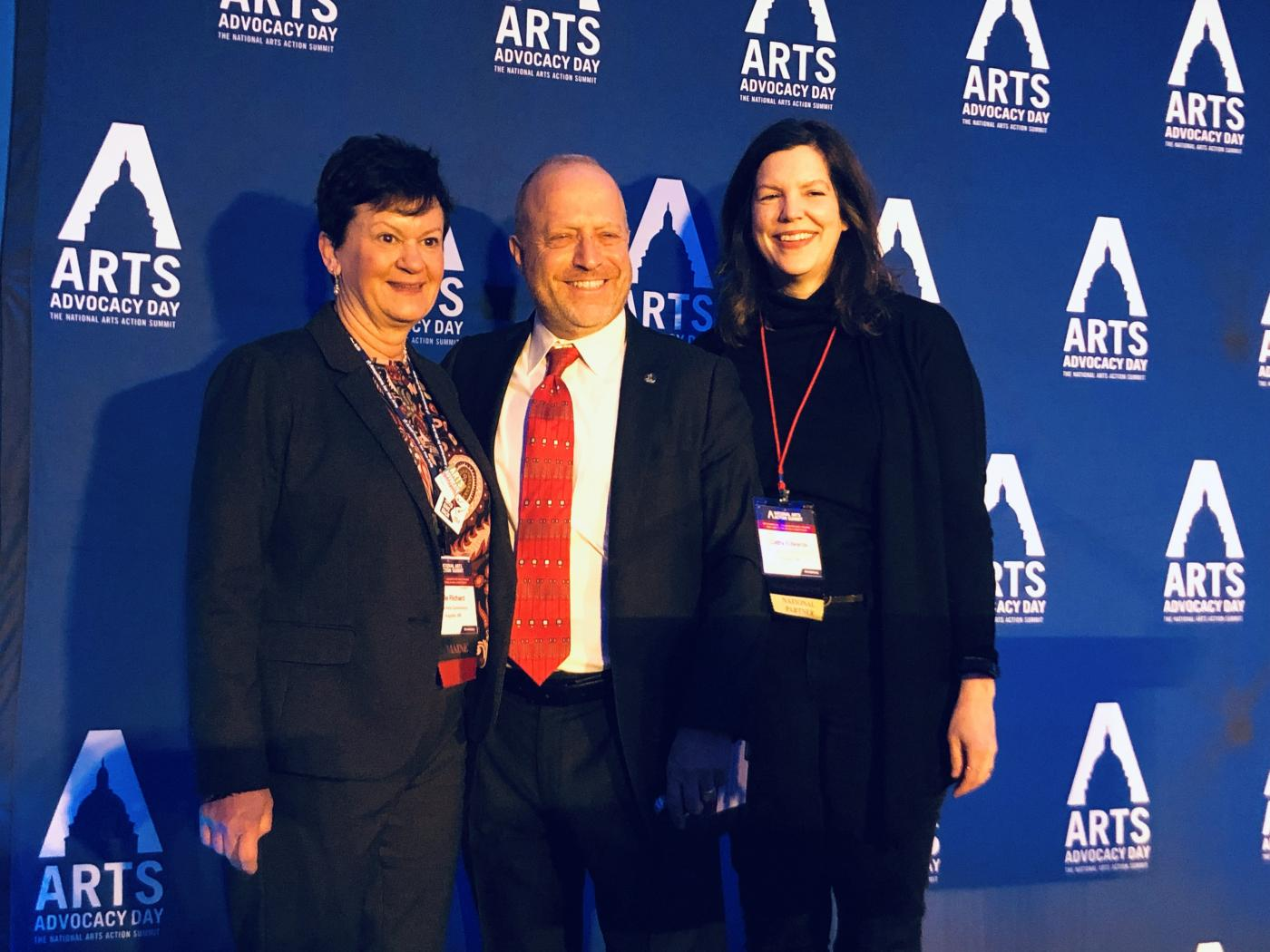Three people pose in front of a banner with the Arts Advocacy Day logo