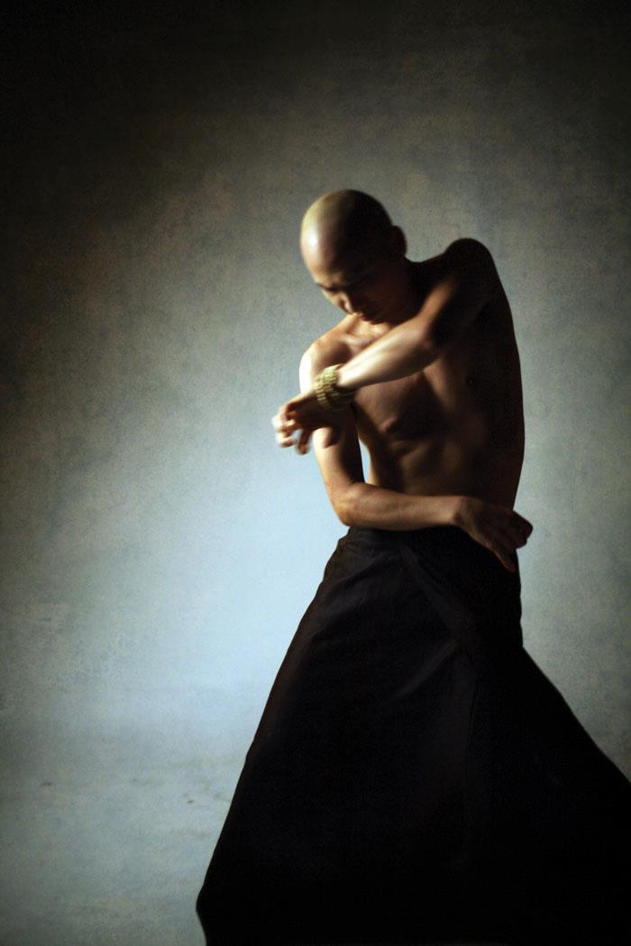 A dimly lit, shirtless dancer performs a butoh full body twist