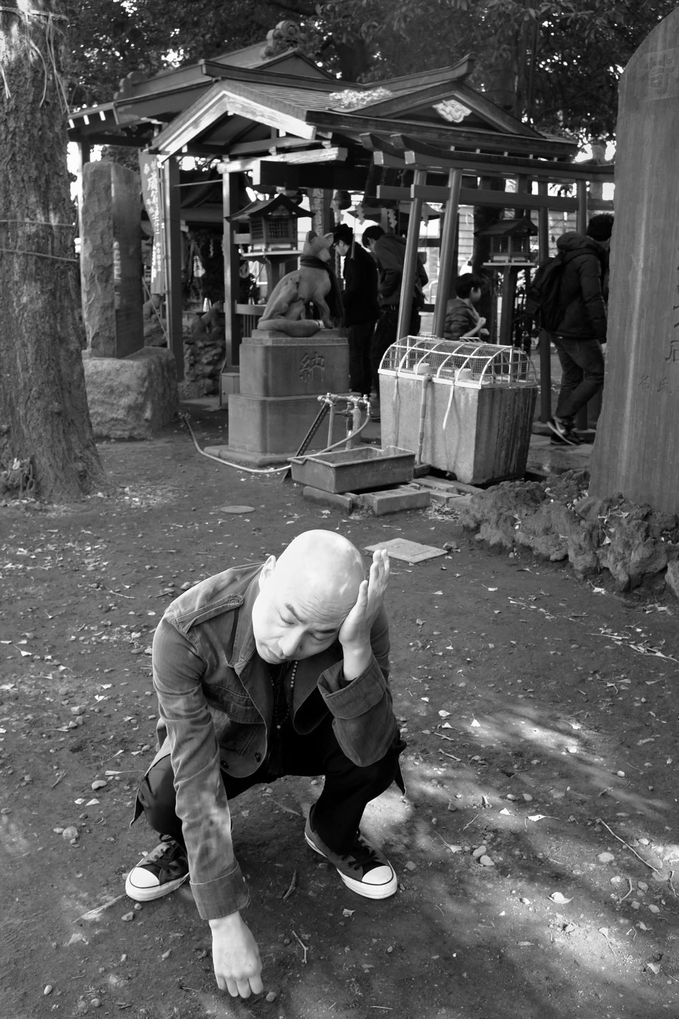 Michael squats next to a Japanese shrine resting his head on his hand in a somewhat distraught emotion.