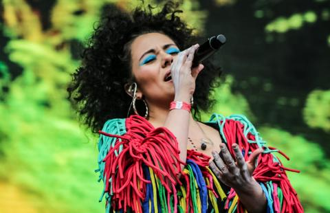 A woman in a bright, fringe covered outfit, eyes closed with bright blue eyeshadow, holding a microphone with head tilted back a bit.