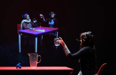 A person at a table holding a glass looking at a projection of  two people at another table holding glasses.