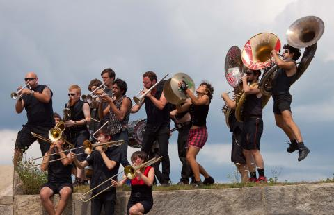 A dozen or more musicians playing brass instruments. A tuba player is leaping. They are outside on a granite-ledged park with a cloudy summer sky in the background.