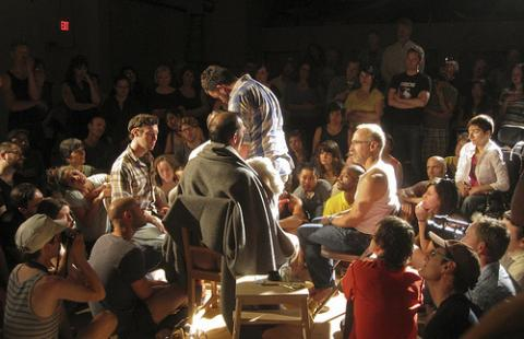 In the center of a crowd, four spotlit people sit in a chairs.