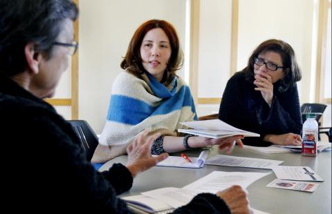Three women sit around a table having a discussion, with papers in front of them.