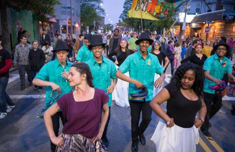 People dance on the street in Boston's Latin Quarter. Men in matching teal tees and black hats dance behind the first row of people.