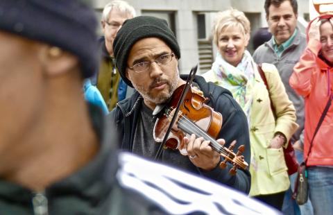 On a city street, a violinist plays in a crowd of people.