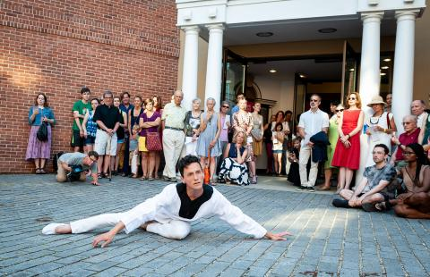 A dancer lays melodramatically on the ground in front of a crowd, outside of a museum entrance with pillars.
