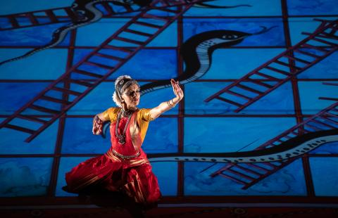 A classical Indian dancer squats low on the stage, gestures with her hands, in front of a blue, back-lit backdrop of painted snakes and ladders.