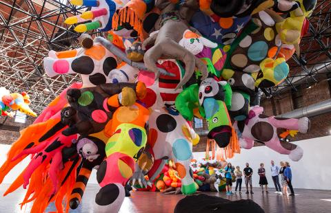 In a gallery with an enormous, colorful sculpture made of lawn inflatables, a group of six folks behold the spectacle.