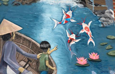 A young boy and an adult, on a boat, point to three koi fish below.