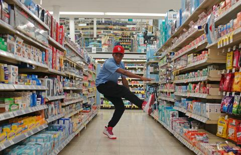 In a pharmacy aisle, a young boy dances.
