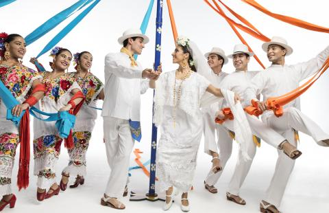 Men and women in traditional Mexican garb dance with ribbons attached to a pole.