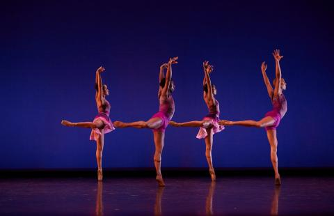 Ballet dancers perform on a stage in purple costumes.