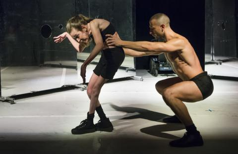 On a stage with mirrors, two dancers, in small black costumes, crouch and slither.