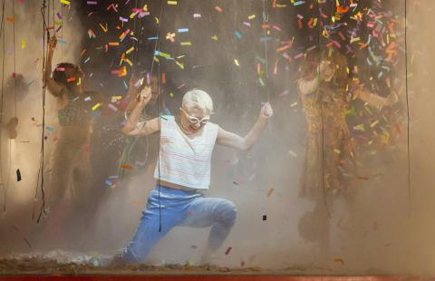 A dancer crouches as confetti falls from the ceiling.