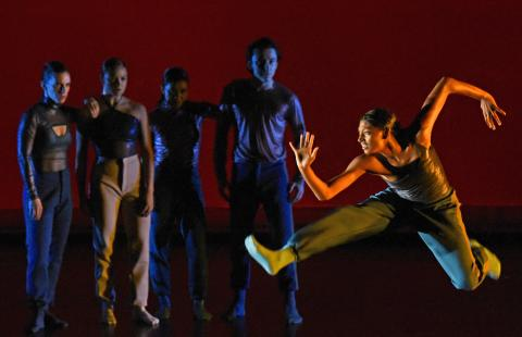 In a spotlight, a dancer leaps while four more dancers look in.