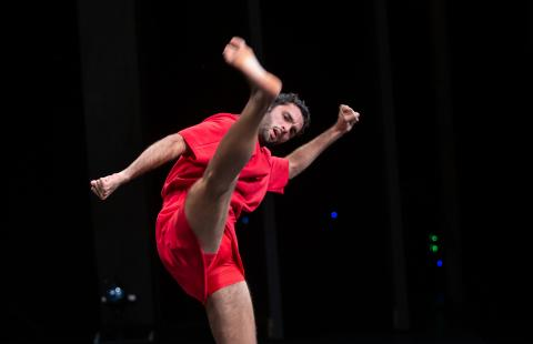 Wearing red, a male dancer kicks his leg up.