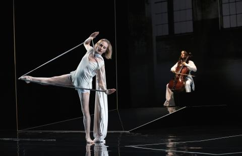 A dancer pushes fabric tied to her wrists with her foot to create a triangle.