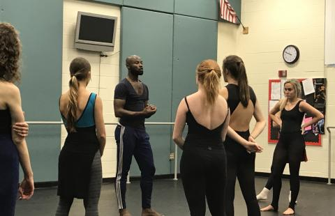 A dance instructor speaks to students in a soundproof room.