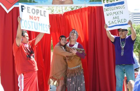 "Two women, in native garb, embrace while two men hold up signs that read ""people not costumes"" and ""indigenous womxn are sacred."""