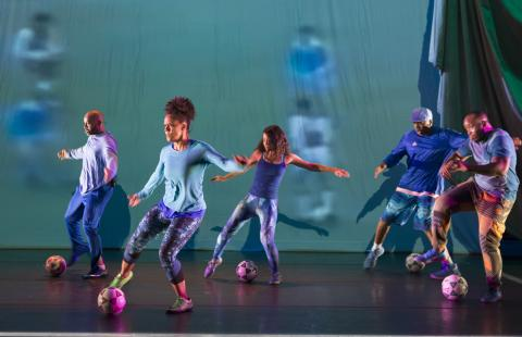 Dancers kick soccer balls around in front of a projection of a soccer game.