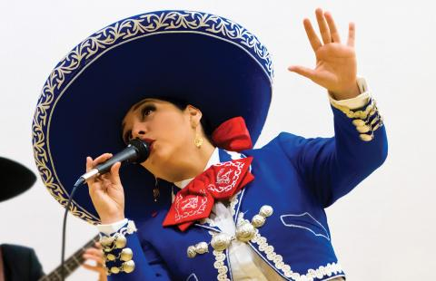 Mariachi singer Veronica Robles, in a sombrero, sings.