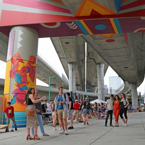 Outside, in an underpass, folks pose with brightly colored murals.