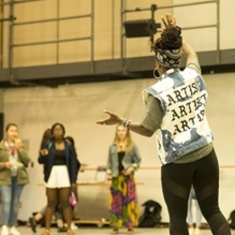 "A woman, in a cutoff vest that reads ""Artist, Artist, Artist"" on the back, speaks with her hands."