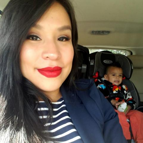 A selfie of Endawnis, with her son in a carseat behind her.