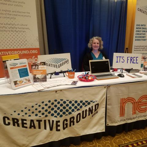 A woman stands behind two tables. One has a CreativeGround logo banner and another has a NEFA logo banner.