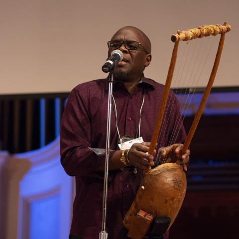 artist Samite Mulondo plays a litungu, a seven stringed instrument, and sings into a standing mic at the 2018 Idea Swap on the Great Hall stage at Mechanics Hall. Samite's eyes are closed as he performs. Blue lighting on the stage and a blank projector screen are seen in the background