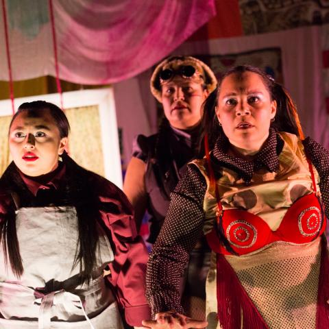 Four women are underlit and wear costumes, like a red bra with gold swirls.