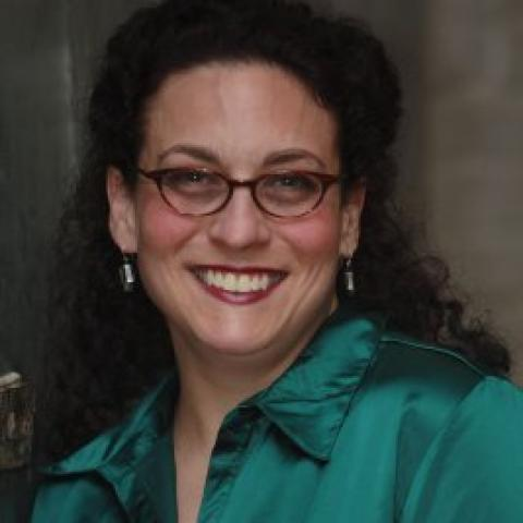 Woman in glasses with her hair pulled back, smiles in her teal button down