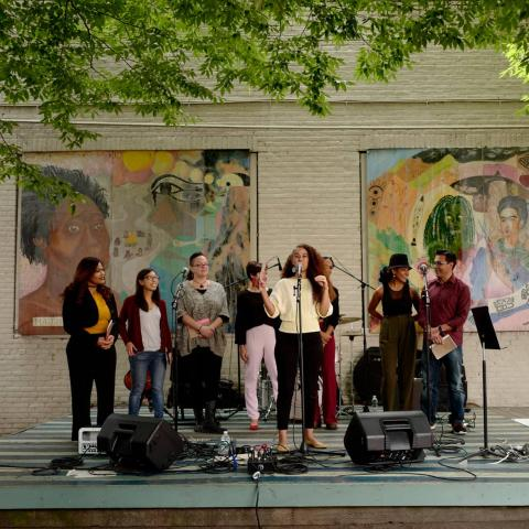 A woman, on stage, with other women presents her project, in front of a wall of murals of powerful women throughout history.