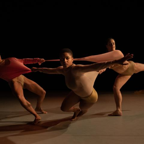 Three dancers perform in a black void with their arms stretched wide.