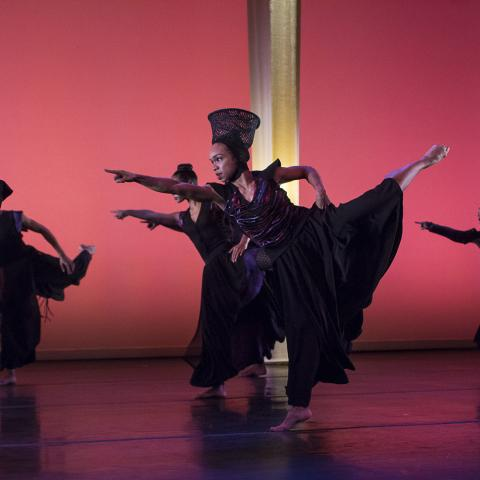 A dancer, in an ensemble of dancers, lifts her leg back and up and points forward.