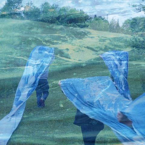 Double exposure. In a field, women carry a blue banner over their heads and a closeup of the blue banner.