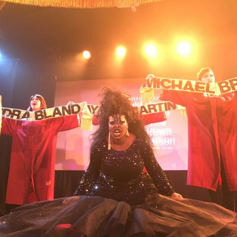 A woman in black sparkly evening wear on stage in front of people in red robes holding banners with names written on them