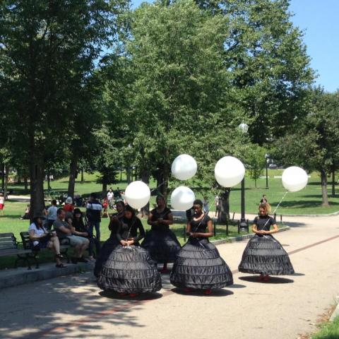 Five dancers in black dresses with white balloons slowly walk through the commons.