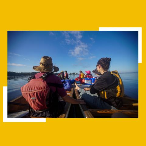 From the canoe, ten canoers travel along the coast on a sunny day.