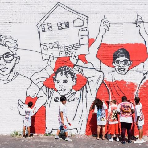 Six kids hang out by a mural of three kids of varying ethnic backgrounds hold up their homes as picket signs.