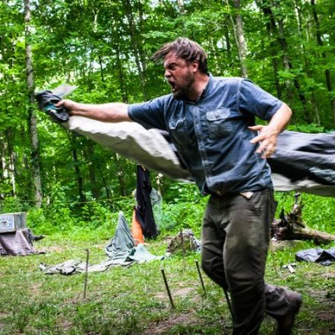 In the woods, a man charges forward with something beneath a coat or fabric.