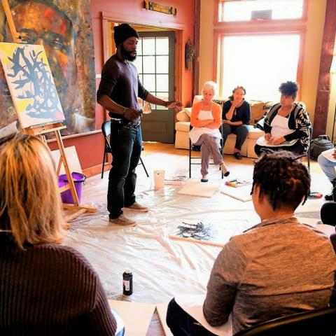 A Black man holding a paint brush with a canvass behind him and surrounded by a semi-circle of seated students.