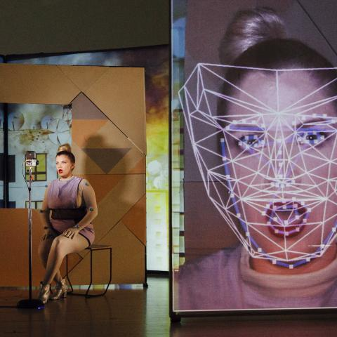 A woman on a stage sits next to a live video of herself that is close on her face and has lines mapped to parts of her face.