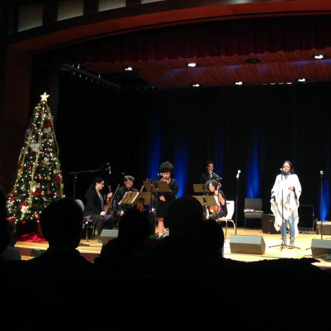 Image of a woman singing into a microphone from a stage, accompanied by musicians. A Christmas tree is on the left.